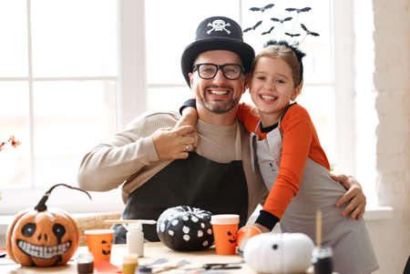 Portrait of happy smiling family dad and daughter wearing Halloween hats smiling at camera and embracing while preparing handmade home decorations, father and little girl enjoying painting pumpkins