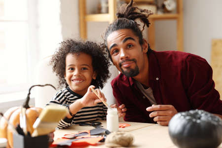 Funny african american family father and little boy smiling at camera while painting Halloween pumpkins together at home, dad preparing decorations with son for all hallows day celebration