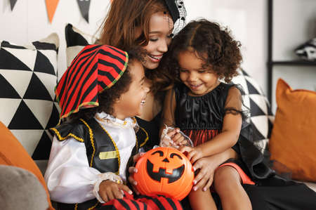 Happy african family smiling mother and two kids celebrating Halloween holiday together at home, mom with son and daughter playing with pumpkin lantern while sitting together on sofa and smiling