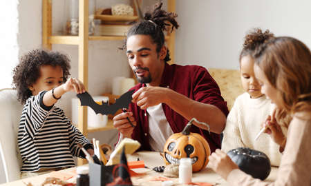 Young african american family mother father and children sitting at table and preparing Halloween decorations at home, loving parents with kids painting pumpkins and cutting paper bats 写真素材