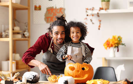Smiling african american family dad and son carving jack o lantern together for Halloween celebration at home, little boy and father smiling at camera while removing pulp from ripe pumpkin