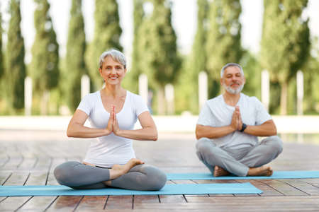 Calm elderly retired family couple practicing yoga outside happy husband and wife sitting on mats barefoot in lotus position holding hands in namaste gesture and smiling at camera. Meditation and mental health 写真素材