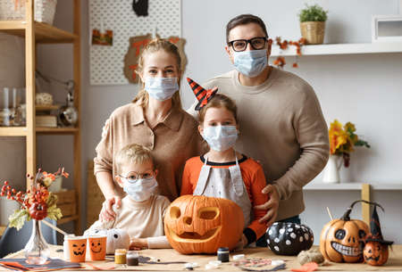 Halloween preparation during COVID-19 quarantine. Young family mother father and children in face masks looking at camera while making jack o lantern from pumpkin together at home 写真素材