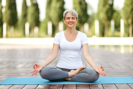 Calm happy senior woman sitting in lotus pose on mat during morning meditation in park, holding hands in mudra gesture and smiling at camera. Mental health and yoga concept
