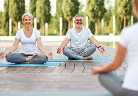 Joyful smiling senior family couple staying in lotus position in front of female yoga trainer, relaxed elderly husband and wife enjoying meditation workout outside in city park. Meditation concept