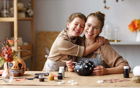 Cute little girl daughter gently hugs mom with closed eyes during while painting Halloween pumpkins together at home, happy family mother and kid preparing handmade decorations for Saints Day party