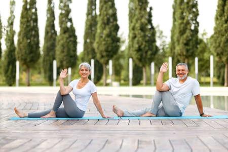 Happy senior retired couple doing partner yoga outside in city park, mature active husband and wife sitting barefoot on mats in eka pada upavistha parivrttasana pose looking at camera with smile 写真素材