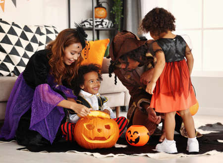 Happy african american family parents and kids in Halloween costumes sitting on floor and looking inside of carved pumpkin jack-o-lantern while celebrating All Saints Day together at home 写真素材