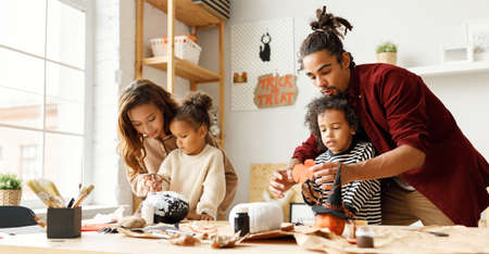 Panoramic banner with young african american family mother, father and children preparing decorations for Halloween at home while sitting at table, painting pumpkins and making paper cuttings together