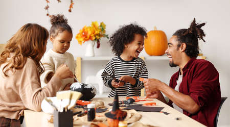 Young joyful african american family mother, father and two kids preparing for Halloween at home, painting pumpkins and making paper cuttings and decorations for Saints Day celebration 写真素材