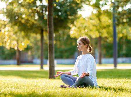 Relaxed slender girl in sportswear sitting in lotus position with eyes closed on yoga mat outdoors in city park on green grass, young sporty lady enjoying meditation on sunny morning in nature