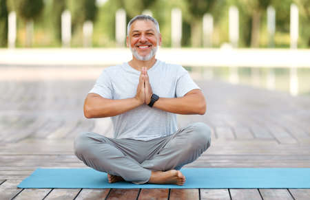 Calm happy mature man sitting in lotus pose on mat during morning meditation in park, holding hands in namaste gesture and smiling at camera, male meditating. Mental health and yoga concept