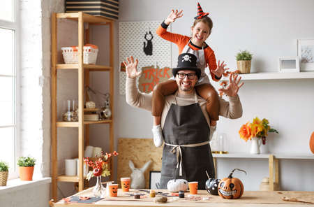Cute little girl sitting on father shoulders and making scary gesture while making Halloween home decorations together, happy family dad and daughter in hats painting pumpkins for Saints Day party 写真素材