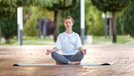 Calm happy young woman sitting in lotus pose on mat during morning meditation in park, holding hands in mudra gesture. Mental health and yoga concept