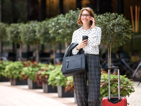 Young successful business lady in formal clothes with suitcase talking on mobile phone while standing on city street, smiling woman with coffee to go calling taxi by smartphone during business trip 写真素材