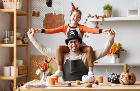 Cute little girl sitting on father shoulders and smiling while making Halloween home decorations together, happy family dad and daughter in hats painting pumpkins for Saints Day party