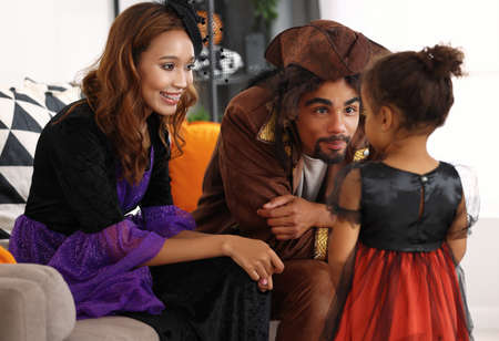 Young african american family parents and cute little girl daughter celebrating Halloween holiday at home, loving mother and father talking with small daughter during all hallows day celebration 写真素材