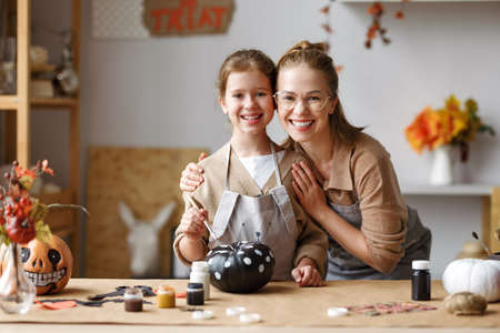 Cute mom gently hugs little girl daughter while painting Halloween pumpkins together at home, happy family mother and kid preparing handmade decorations for Saints Day party 写真素材