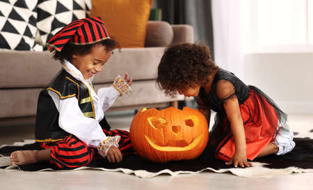 Happy excited african little boy and girl wearing Halloween costumes sitting on floor and playing with big jack o lantern, children looking inside of carved pumpkin while celebrating All Saints Day