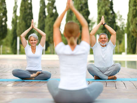 Joyful smiling senior family couple staying in lotus position with folded hands raised up of female yoga trainer, relaxed elderly husband and wife enjoying meditation workout outside in city park. Meditation concept