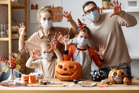 Halloween preparation during COVID-19 quarantine. Young family mother father and children in face masks making scary gesture and scare while making jack o lantern from pumpkin together at home