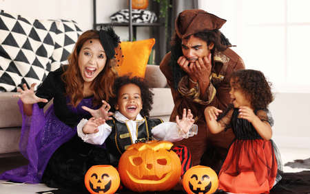 African american family in Halloween costumes making scary gesture while sitting with jack o lantern