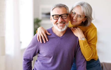 Portrait of happy beautiful senior caucasian family couple in love smiling at camera at home 写真素材