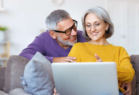Beautiful mature family couple looking at laptop with smile on face while spending time together