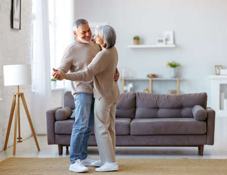 Happy senior couple in love looking at each other with tenderness, dancing together in living room