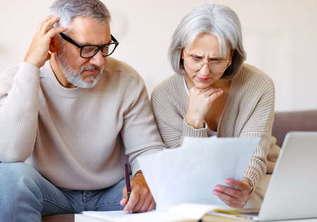 Worried senior family reading financial documents or notification letter with bad news from bank 写真素材