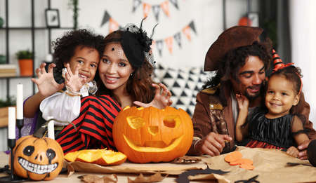 Happy african family parents with kids preparing Halloween decorations at home 写真素材