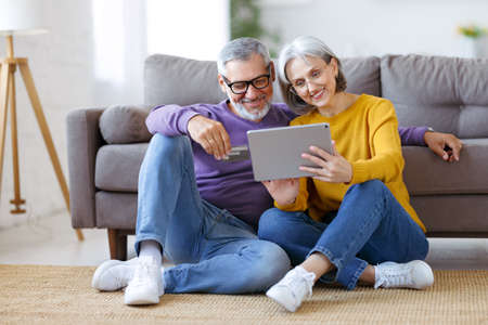 Beautiful mature family couple looking at tablet with smile on face while spending time together
