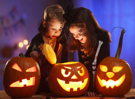 Excited children in Halloween costumes looking inside glowing jack o lantern in dark decorated room