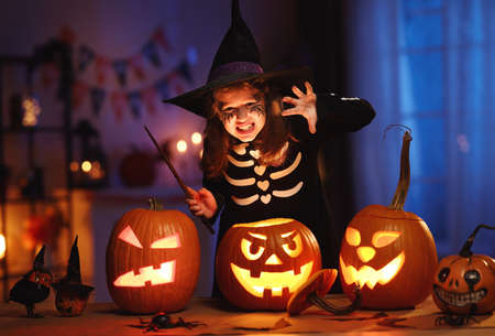 Little girl in witch hat and skeleton costume with magic wand in hand with frightening face
