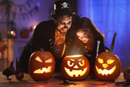 Happy family father and daughter in Halloween costumes looking inside of glowing jack-o-lantern 写真素材