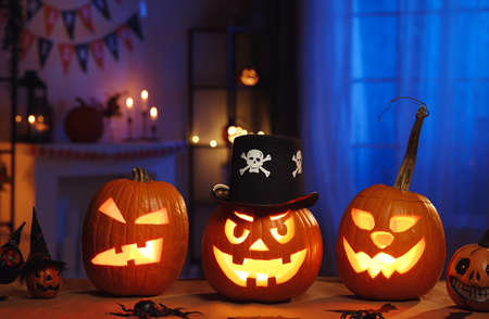 Spooky halloween home decor in dark room decorated with carved pumpkins and spiders
