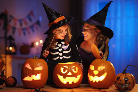 Happy family mother and little girl daughter in witch costumes celebrating Halloween at home 写真素材
