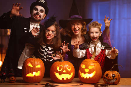 Young family mother father and children in Halloween costumes celebrating all hallows eve at home