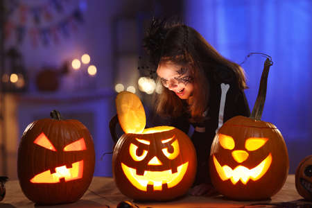 Little girl in Halloween costume and makeup with glowing jack-o-lantern during Halloween celebration 写真素材