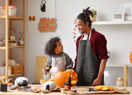 Cute happy little african american boy carving Halloween pumpkin with father at home