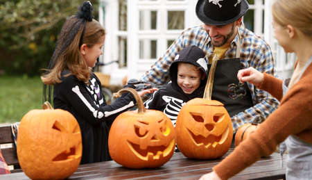 Happy young family in Halloween costumes carving pumpkins together in backyard 写真素材
