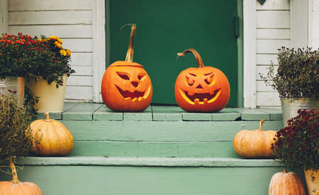 House with halloween orange pumpkin decoration, jack o lanterns with spooky faces on porch