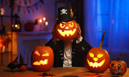 Man in Halloween costume holding glowing jack-o-lantern carved pumpkin in front of face 写真素材