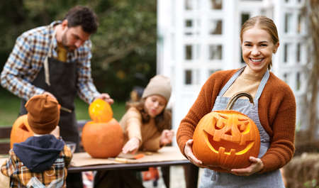Smiling woman with jack-o-lantern smiling at camera while carving pumpkins with family in backyard
