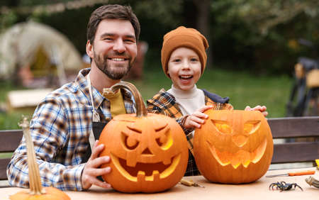 Smiling father and little boy son carving pumpkins in backyard