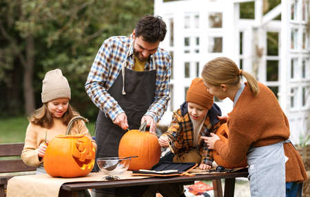 Happy young family carving pumpkins in backyard, children making jack-o-lantern with parents