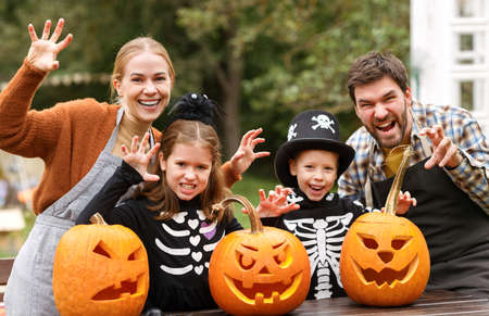 Young caucasian family mother father and children in Halloween costumes at decorated backyard 写真素材