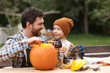 Father and son carving pumpkin for halloween in backyard