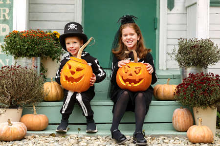 Two happy kids in Halloween costumes sitting on porch of their house with carved pumpkins 写真素材