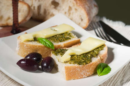 Organic ciabatta bread with pesto dressing with cheese and black olives photo